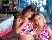 beautiful sisters little girls eating chocolate ice cream in mexican market