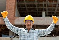 successful engineer smiling with arms up in a construction