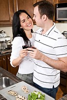 A beautiful interracial couple preparing food in the kitchen