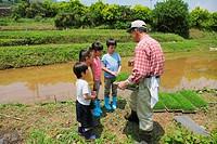 Senior Man Guiding Children On a Farm
