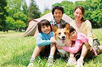 Japanese Family Having Fun In a Field With Pet