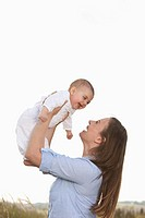 Germany, Bavaria, Mother holding aloft 2_5 months baby girl, smiling