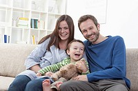 Germany, Bavaria, Munich, Family on sofa in living room, smiling