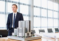 Businessman standing in conference room with model building