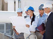 Business people in hard_hats reviewing blueprints outdoors