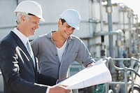 Businessman and worker reviewing blueprints outdoors