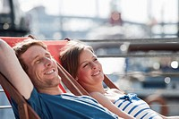 Germany, Hamburg, Couple relaxing in deck chair looking away, smiling