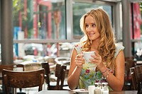 Germany, Munich, Teenage girl drinking coffee in cafe, smiling