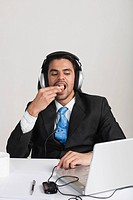 Businessman eating snacks while listening to headphones at the desk