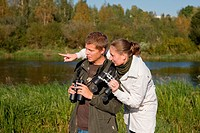 Young couple birdwatching with binoculars by river water pointing away