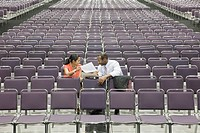 Black businesspeople talking in empty conference center
