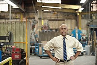 Black manager standing in factory