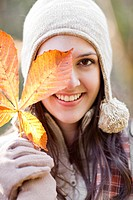 Mixed race woman in cap holding autumn leaf
