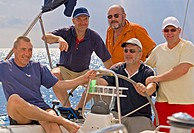 Group photo of five men on a sailing yacht