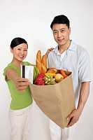 Man holding a bag of groceries, woman showing credit card