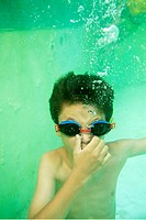Young boy wearing swimming goggles and holding his breath underwater in a pool, Provence, France