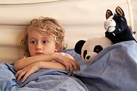 Little girl watching TV in bed, surrounded by her favourite stuffed animals