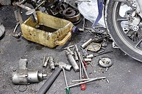 A dismantled Yamaha motorbike with engine parts and tools scattered on ground