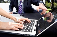 Business couple using a laptop in the park