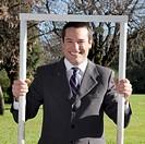 Portrait of a businessman holding a frame
