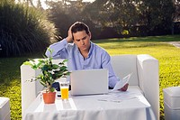 Man sorting out bills in front of a laptop