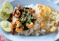 stir fried prawn with basil and fried egg top on rice, typical lunch time food in bangkok, thailand