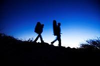 Man and woman hike with crash pads.