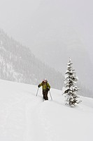 Young woman ski_touring through forest.