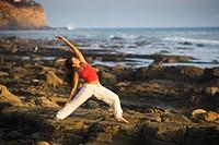 Woman doing yoga on ocean´s edge.