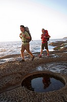 Hikers at waterhole on rocky coast.