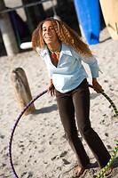 Woman hula_hoops on beach.