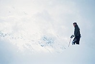 Skier taking in the view on massive slopes high above Chamonix Valley.