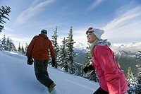 A man and woman hike in ski gear through untouched snow with Mt. Rainier in the background.