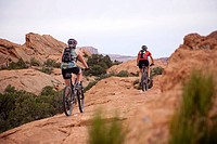 Two women mountain bike one of the Slick Rock routes in Moab Utah.