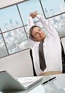 Businessman sitting at desk, stretching arms, smiling