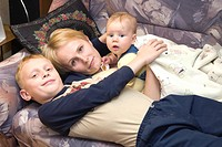 Happy Mother with Embracing Caucasian Kids, Family on Bed