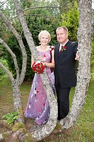 Happy Caucasian Wedding Couple by Pine Tree Trunk