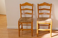 Two wooden chairs, with wickerwork seats