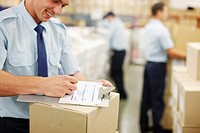 Worker writing on clipboard in shipping area