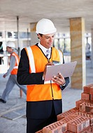 Businessman looking at clipboard on construction site