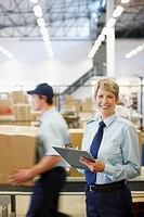 Worker with clipboard in shipping area