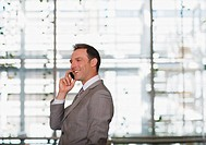 Businessman talking on cell phone in office
