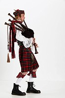 scotsman dressed in plaid pleated skirt playing the bagpipe in profile