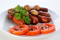 grilled beef sausages and tomato on a plate