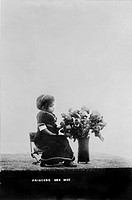 Princess Wee Wee, African American dwarf, full_length portrait, seated, facing right, with bouquet of flowers, 1915.