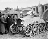 Henry Ford 1963_1947, and Military officers, inspect a multi_wheeled vehicle with caterpillar tracks. 1921.