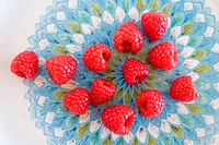 Raspberries on a colored porcelain plate