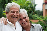 Smiling Hispanic men hugging