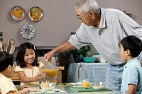 Asian grandfather serving grandchildren orange juice