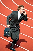 Happy businessman on cell phone sprinting fast on track with briefcase.